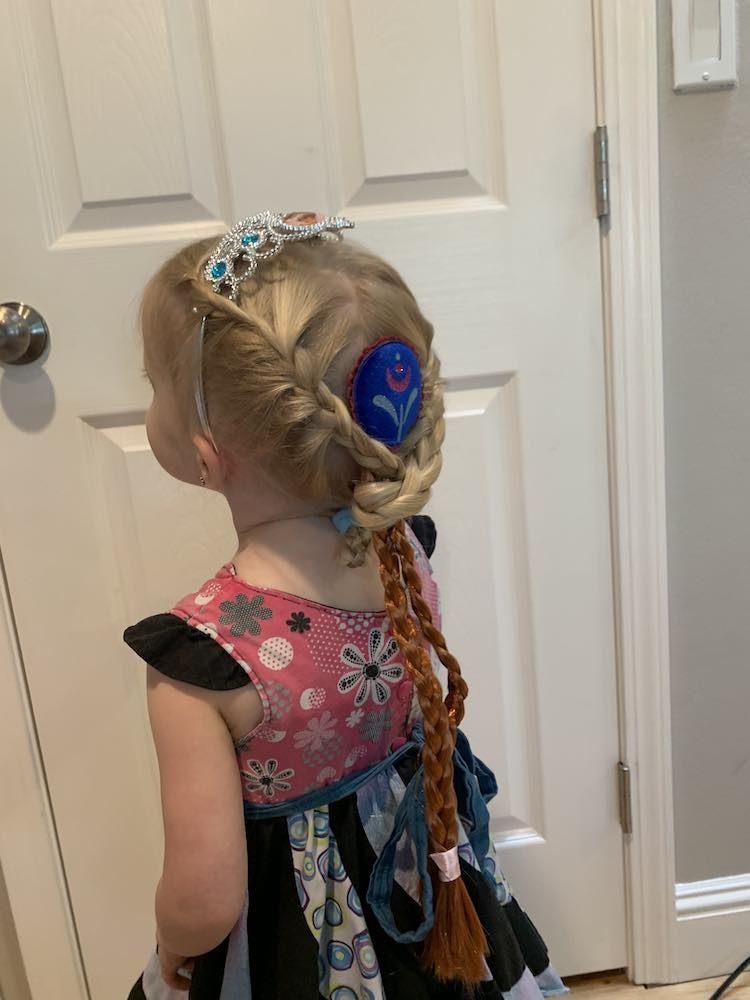 Photo showing Zoey's back with the dangling Anna braids. Her hair is french braided over the sides of the crown and then at the bottom the braids switch to normal and the Anna braids, with the blue centerpiece, is clipped between them. Zoey's braids are wrapped around the Anna braids and then pony-tailed in place so they're less visible.