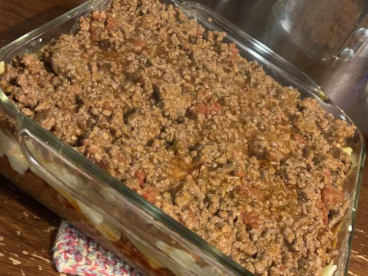 The clear casserole pan is mostly filled. The top is coated in meat and tomato mixture with a hint of pasta showing on the right side. From the front side you can vaguely see the pasta and cheese layer sandwiched between the two meat layers.