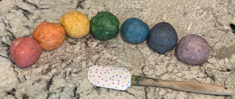 Image shows a row of sparkly colored balls of playdough and a spatula. The balls are red, orange, yellow, green, blue, black, and purple.