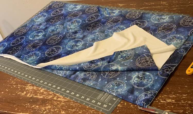 The fabric is folded in quarters, like the previous picture, but the top half is cut, lengthwise, up to the fold while a pair of sewing scissors sit poised to cut the other half.