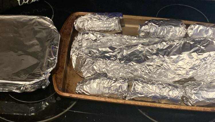 Closeup of the aluminun wrapped food sitting on the stovetop. To the left is a nine by nine casserole dish containing the beans, To the right is a sheet pan with the wrapped ribs down the center and the wrapped corn on the cob along either side.