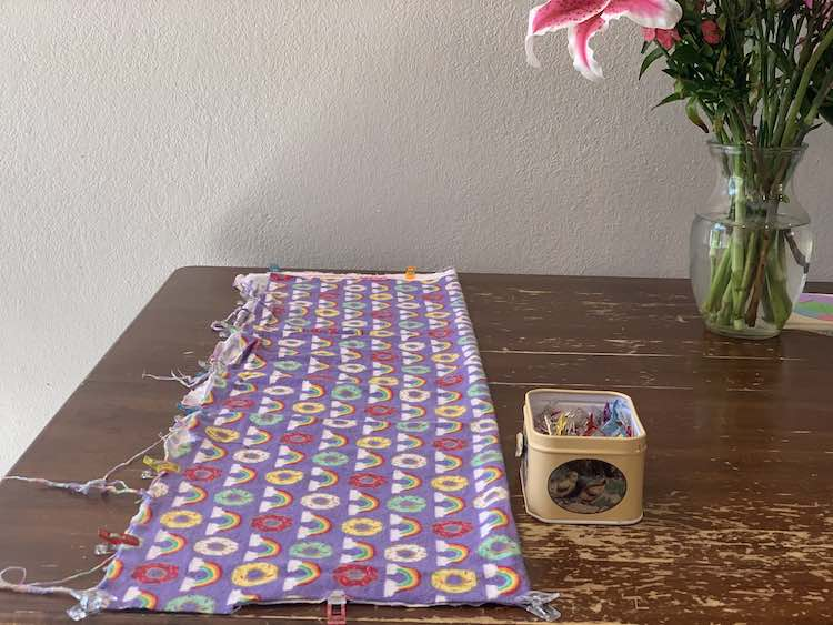 The photo shows the kitchen table with the purple fabric (with rainbows and donuts on it) folded in half. There's a container of sewing clips next to the fabric and some of the clips are attached along the left side and either end of the fabric. To the right top of the photo there lies a a vase with the bottom part of a lily shown.