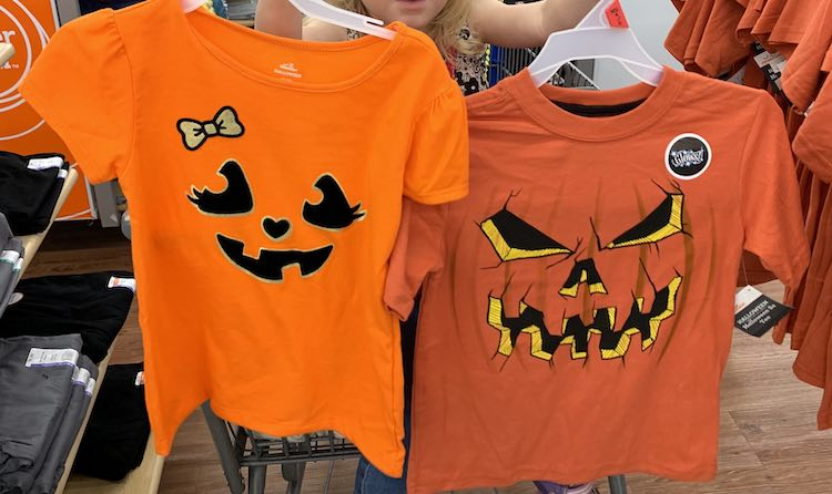 Image shows Zoey sitting in a shopping car at Walmart. She's holding up two shirts that, mostly, covers her up. The one on the left is a brighter orange, thinner fabric, with a cuter jack-o-lantern shapes and bow. The one on the right is slightly scarier with pumpkin curved vertical lines and a sticker letting you know it glows.