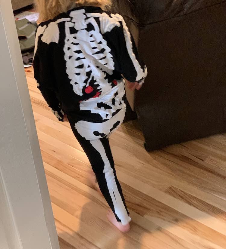 The back of Ada is shown while she skeleton walks away from the camera towards the living room.