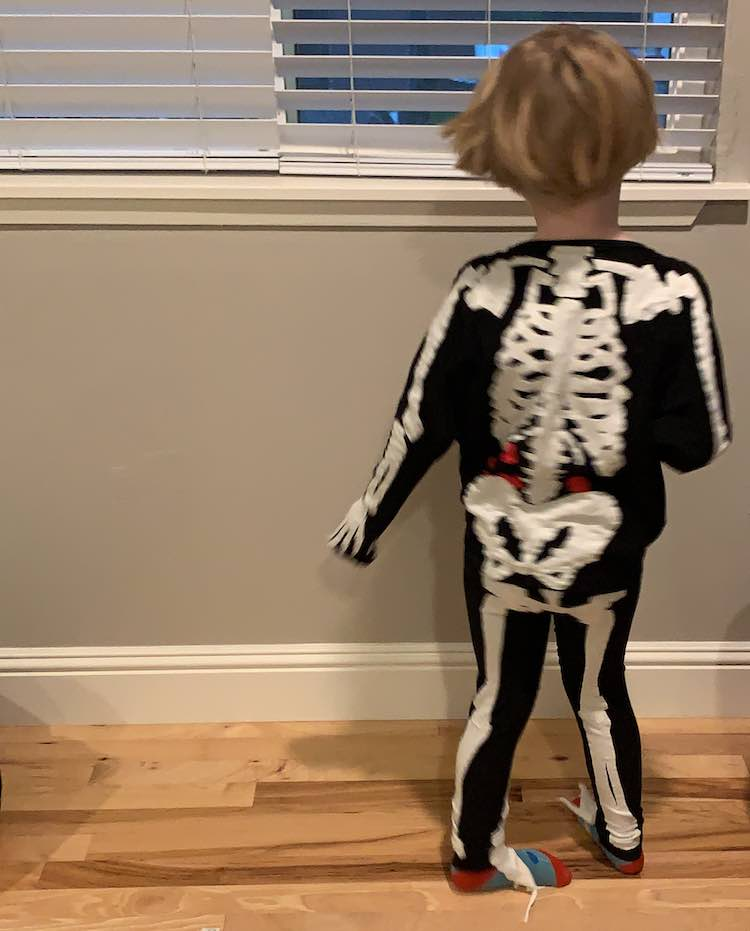 The back of the skeleton is facing the camera as she spins in the costume.