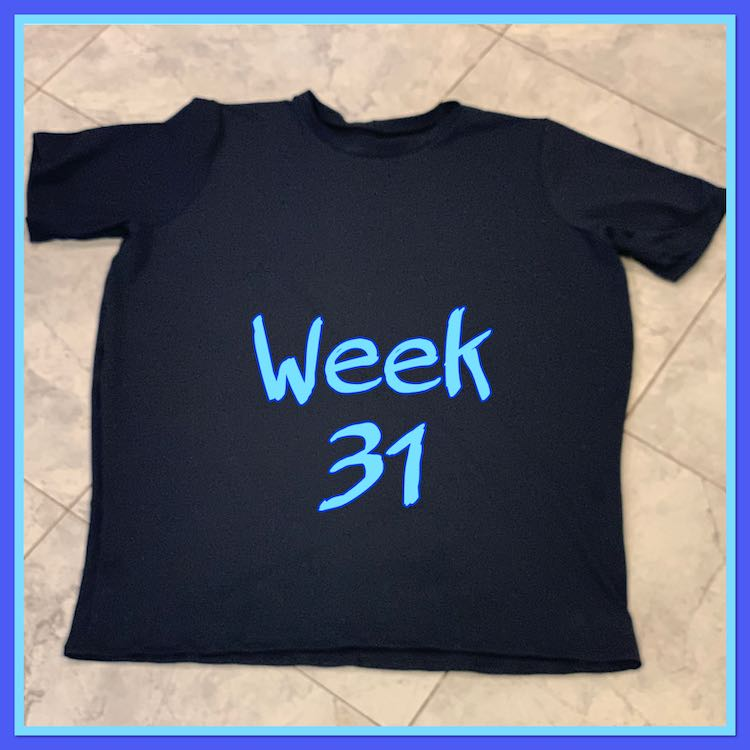 "Image shows a simple black t-shirt laid out on the tiled floor with the words ""week 31"" in blue over the center. The image is outlined in light and then dark blue."