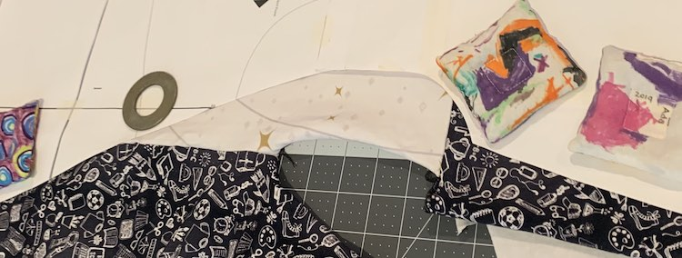 Image shows a part of the paper pattern with the fabric, both white and black, extending past the edge of the pattern. Underneath it all sits my cutting mat and above it all sits four of my pattern weights.