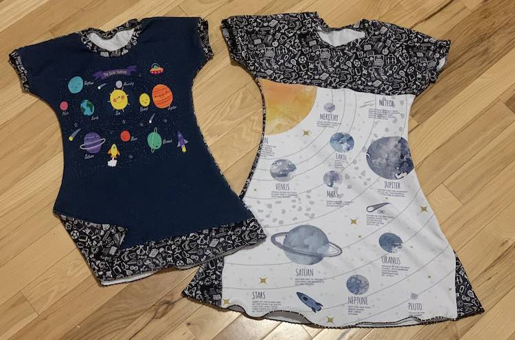 Flat lay of the two dresses side by side. The one on the left are cartoon-ish planets on a navy blue background with the school doodles for the bands along the neckline, cuffs, and along the bottom of the dress. The other dress had a diagram of the planets with text about each one added. The doodle fabric for the bands don't stand out here as the coordinating doodle fabric was added to the bottom sides of the panel along with the top bodice.