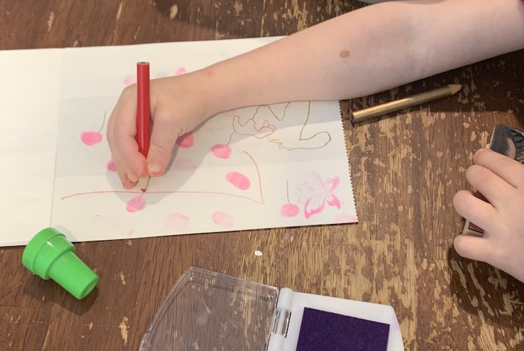 Over view of Zoey drawing a red line coming from one of the many pink fingerprints on the flattened paper bag in front of her.