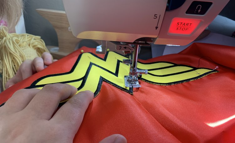 Closeup of the logo on the cape as it's being sewn together in my sewing machine. My left hand holds the fabric while my right hand snapped the photo. To the left you can see Ada's hand, a doll's head, and part of Ada as she watches.