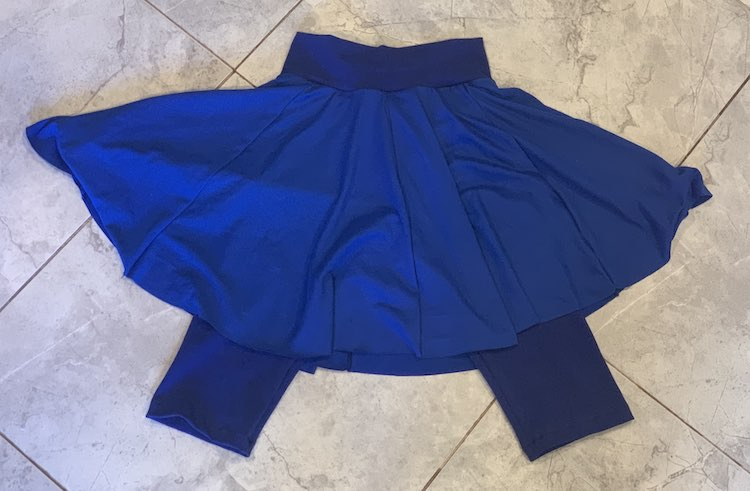 Photo is an overview of a blue skort laid out on the floor. I used a darker fabric for the leggings and waistband and a lighter fabric for the full skirt.