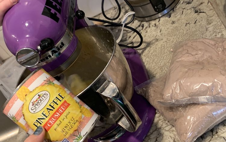 The purple stand mixer is currently beating the contents of the bowl. Ada's hand is resting on top of the mixer while I hold the emptied can of crushed pineapple up for the camera. Off to the right, on the counter, sits the two unopened bags of brownie mix.