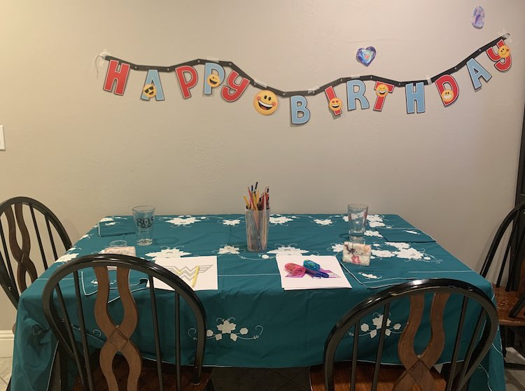 A wooden table covered in a blue/green table cloth with napkins, glasses, papers, and coloring pencils on it. Around the table sits four chairs and above the table is a Happy Birthday banner on the wall.