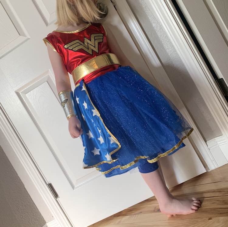 Closeup view of the front of Ada's costume with the homemade leggings poking out the bottom of the dress.