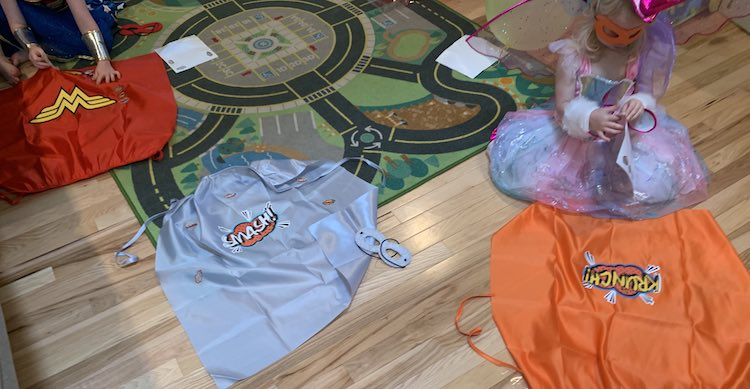 View looking down at the floor of three capes: red, silver, and orange. I quickly finished attaching the stickers to the silver cape while the kids are still crouched in front decorating them.
