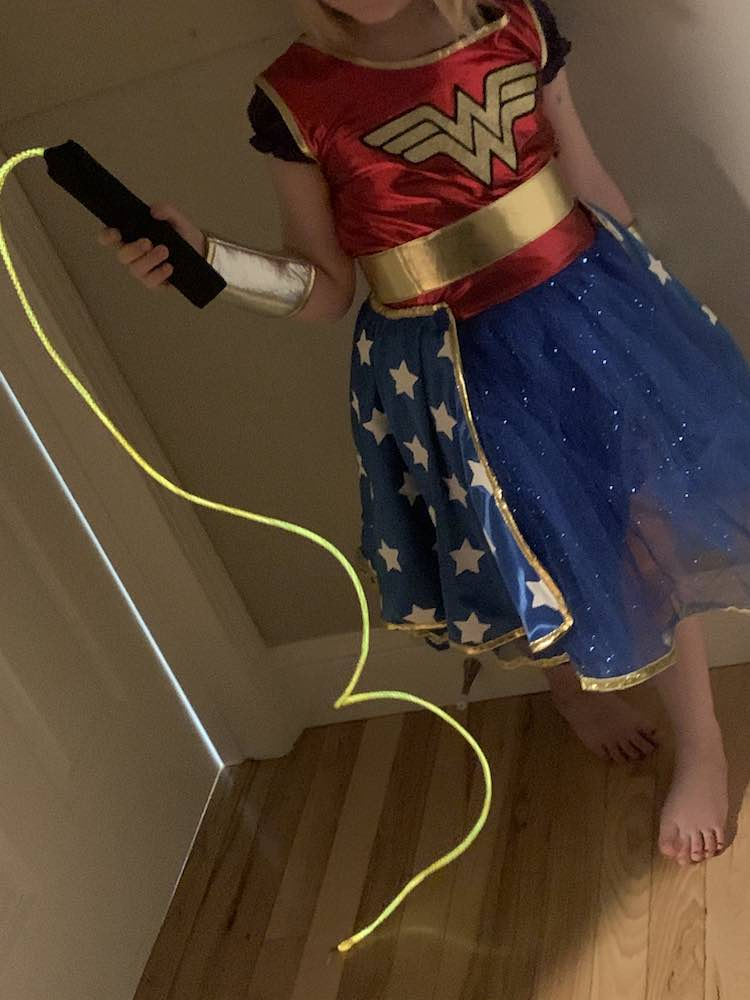 Wonder Woman holding up her lasso of truth. The black handle is in her hand and the glowing lasso hangs and drapes onto the floor.
