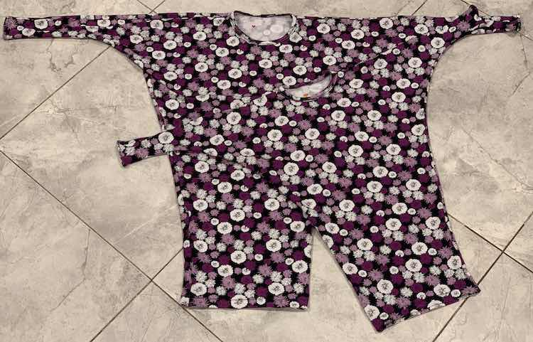 Image shows a flat lay of the two finished flowered tunics laying on the kitchen floor. Inside the neckline you can see, if you look closely, a little red or orange heart on the white-ish inside.