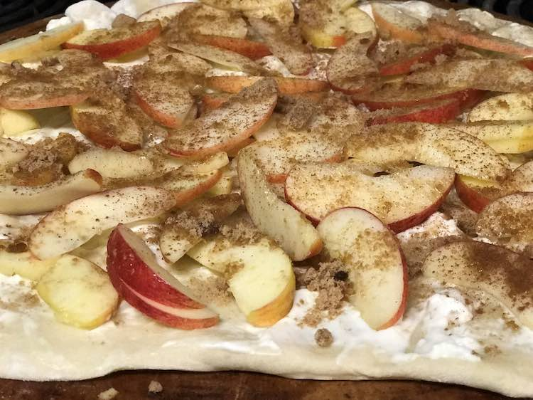 Image shows a closeup of a beige pizza crust with white cream cheese, sliced apples, topped with brown sugar and cinnamon.
