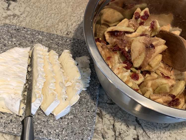 Image shows a metal bowl filled with sliced and peeled apples, craisins, and seasonings. Beside it sits a small marbled cutting board with sliced brie cheese with the rind on.