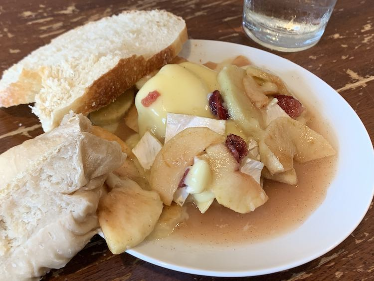 Image shows a plate with a pile of brie coated apples and crasins on it sitting in syrupy sauce. Leaned against the side of the plate are two slices of bread; in the back sits a dried slice of store bought bread while in the front sits a soft dumpling-like slice.