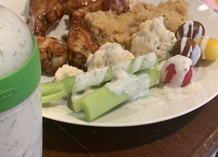 Image shows part of the OXO salad dressing container in the foreground. Behind it sits a plate with chicken wings, quinoa, and veggies drizzled with the ranch dressing.