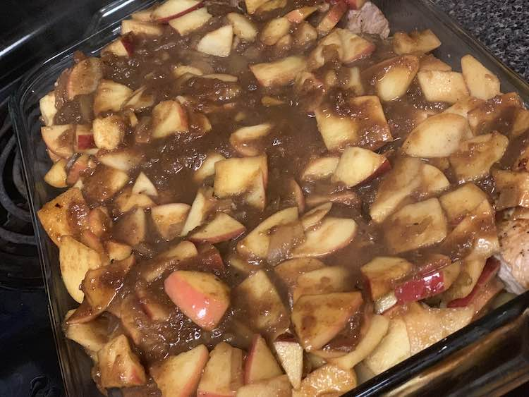 Image shows a closeup of the glass casserole dish filled withe chunks of apples and brown sauce. The pork chops are mostly hidden underneath.