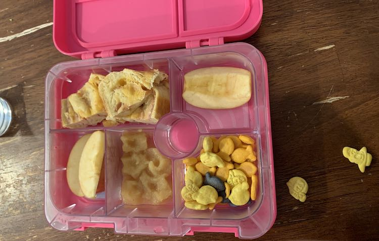 Image shows an open pink divided lunchbox. The section being shown shows star-shaped applesauce shapes. The other cubbies hold sandwich bread, apples, and a mix of cheese crackers.