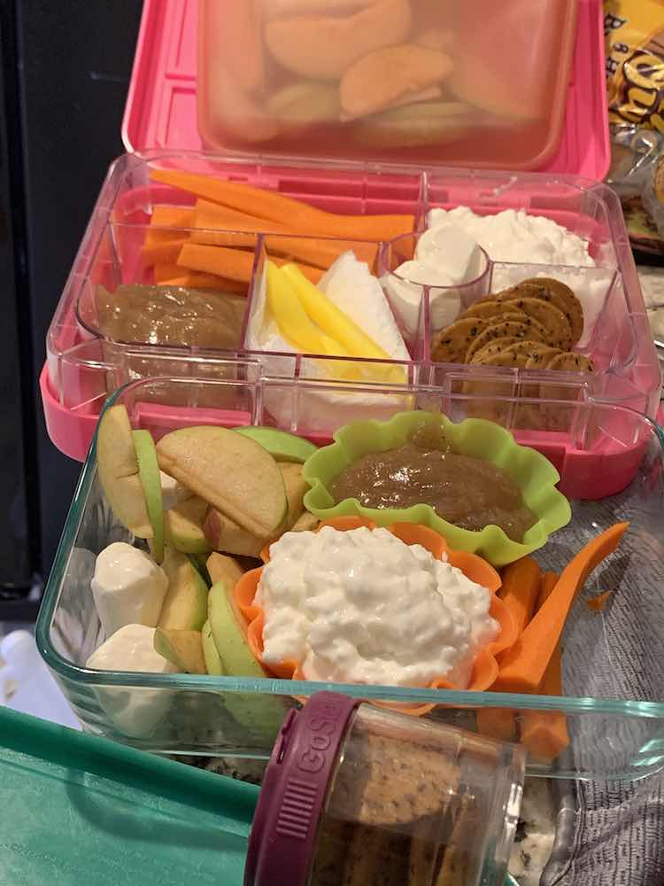 Image shows an opened lunchbox with an apple filled stasher bag leaned against the lid and a glass container, with similar stuff, in front of it. There's a small plastic container of crackers in the front. The dried, wet, and sauces are separated by the lunchbox sections of silicon cupcake liners.
