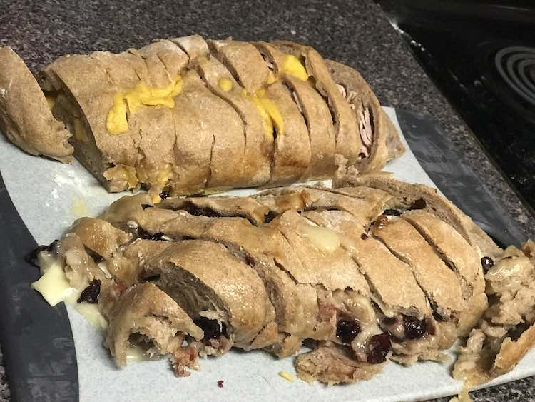 The image shows parchment paper with two loaves sitting on it. Both loaves are sliced. The back loaf has cheddar cheese on it and some deli meat showing at either end. The loaf in the front shows craisins and brie oozing out from the sliced sections.
