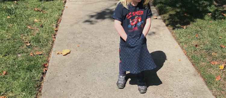 View of Ada's monster truck dress with matching tire tread fabric. Ada's standing straight with her hands in her pocket enjoying the kangaroo pocket in the skirt.