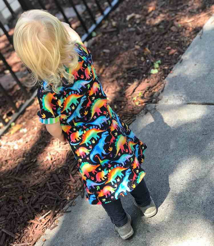 View of the back of Zoey's black dress with rainbow dinosaurs on it. You can see the back of the dress is all one piece with no seam so the dinosaurs aren't interrupted.
