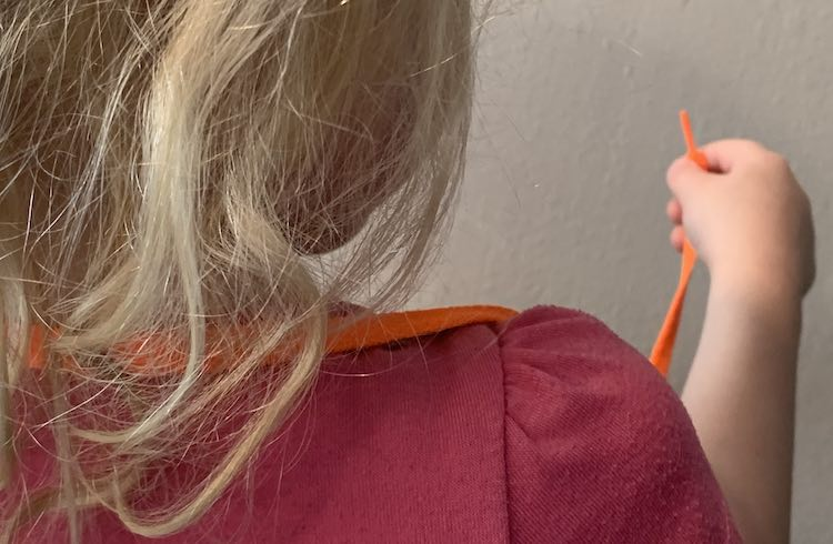 View of the back of Zoey's head and a shoulder. The orange shoelace is looped around her neck with the mask hidden in front of her. Her right hand is holding an end of the shoelace.