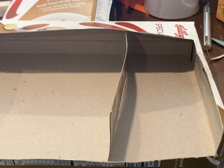 Image shows the cereal box on it's side with the top and front cut off. Inside a strip is loosely placed vertically to act as a divider making one large and one small space in the box.