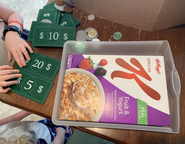 Image shows the plastic drawer sitting on the table with the Kellogg's Special K cereal box laying inside. Off to the side Ada and Zoey are standing by the table organizing the bills and coins.