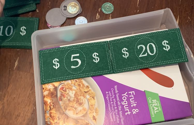Image shows the cereal box within the plastic drawer again. There's a $5 and $20 bill side by side. The $5 is against the back of the drawer while the $20 bill beside it overlaps the side of the box and lays over the top of the drawer's front.