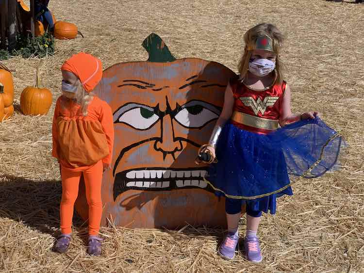 Image shows a painted wooden pumpkin with a Zoey costumed pumpkin and an Ada Wonder Woman standing by it. Around it lays straw on the floor and actual pumpkins off to the side.
