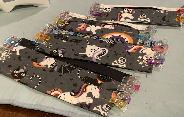All four masks are laid out on the blue ironing mat on the table. The top of each shows a small strip of the outer fabric as it was folded in. Other than that they all have the same grey starred fabric with horned unicorns, pumpkins, cats, and skulls tossed around. The pleats make it appear like those old paper images that you fold in to change the image.