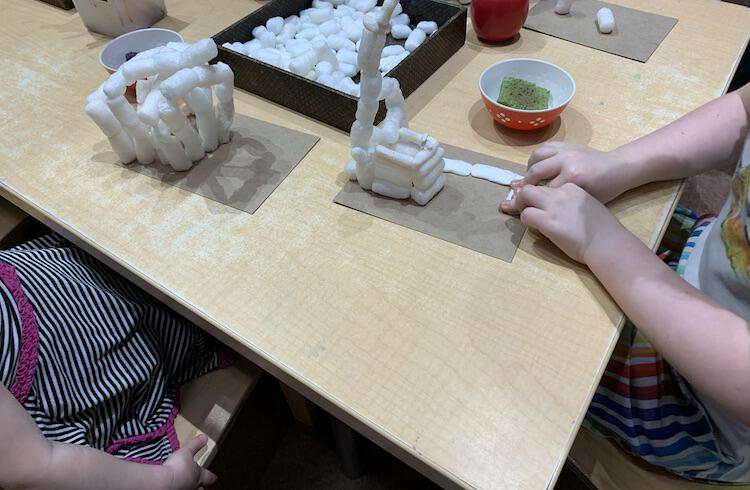 Image shows a table that two kids are sitting at making a biodegradable packing peanut sculpture on a piece of cardboard. In the middle sits a tray of more packing peanuts and beside them sits a bowl with a damp sponge inside.