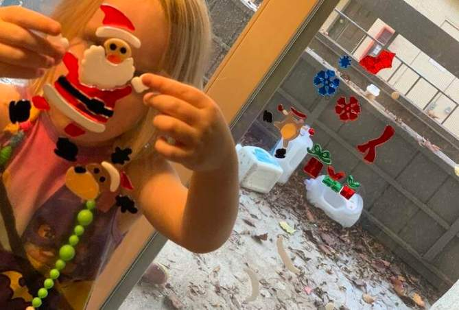 Image shows a window gel cling Santa being held up in front of Ada's face. Behind her is the patio door with some of the other window gel clings already attached on.
