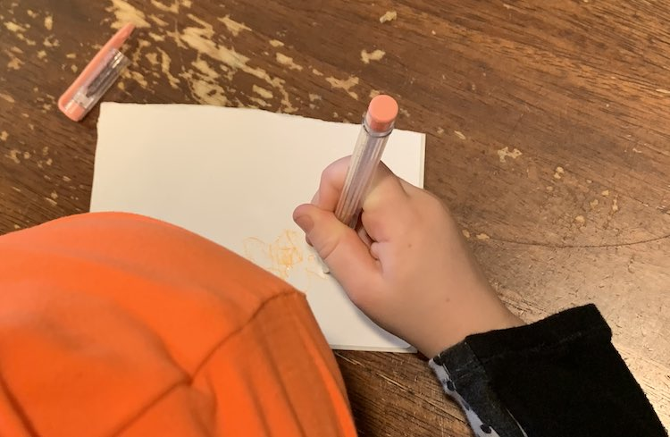 Image is take from above Zoey looking down at the table. You can see part of her pumpkin hat and her hand while she doodles on the sticker with an orange-y peach gel pen.