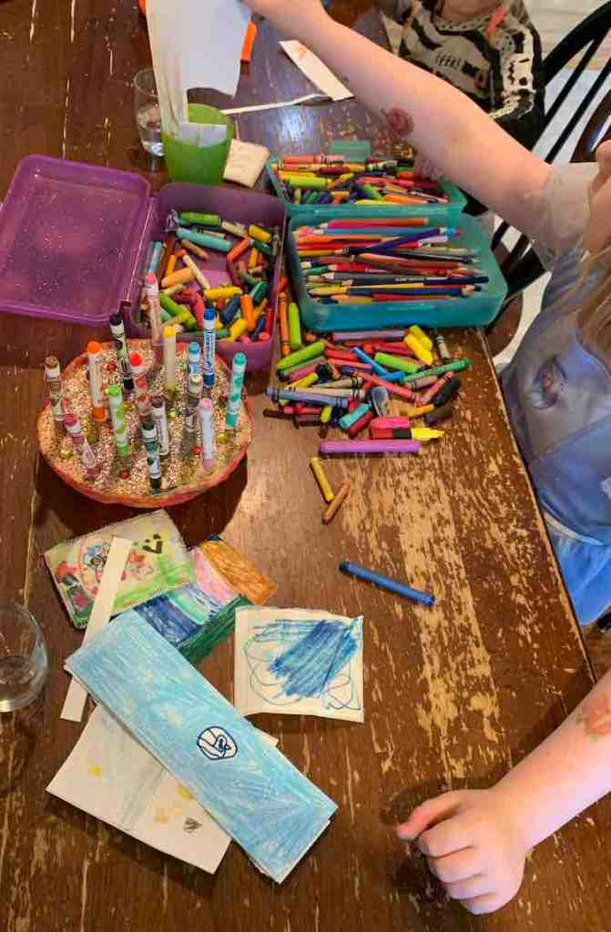 Image shows the table, stretching from the bottom of the image to the top. Ada is grabbing a new blank sticker to design another to add to her finished pile in front of her. Between the kids sits their shared art supplies.