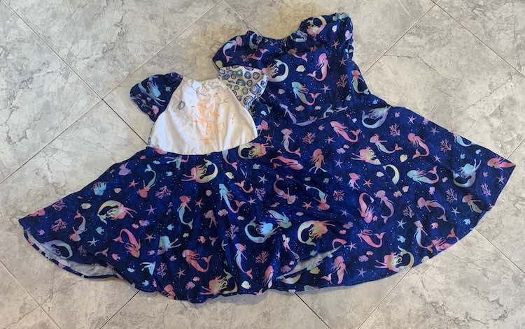 Flat lay of the two dresses on the kitchen floor.