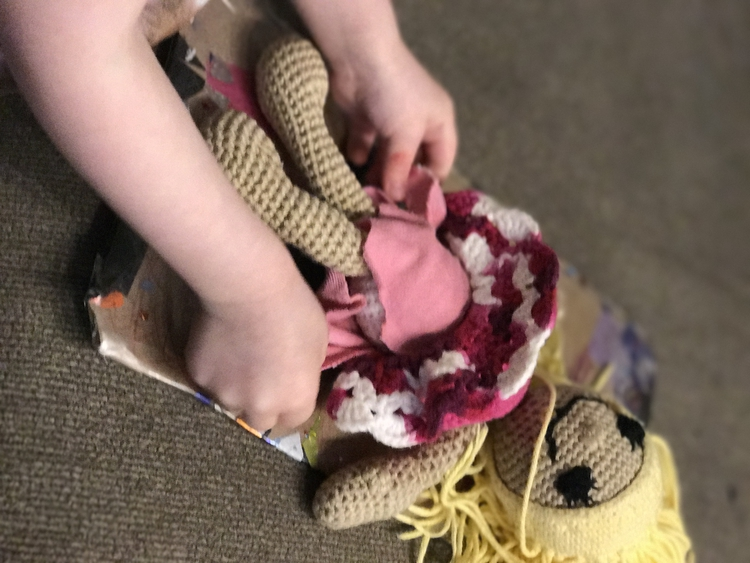 Image is the same from the Pinterest collage shown at the top of the post. In this Ada is closing the diaper using the Velcro while the doll smiles up at her on the changing pad.