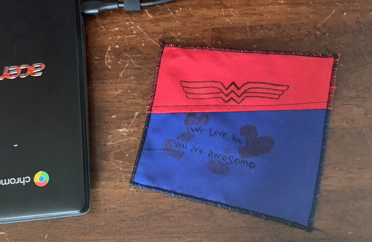 Image shows the finished black edged red and blue Wonder Woman coaster on a brown surface next to the laptop.