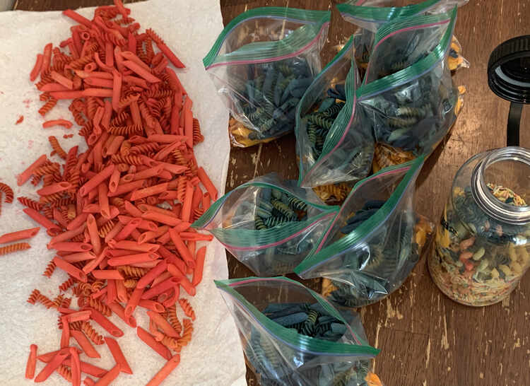 Image shows seven bags of blue and yellow (hidden) pasta laid out in the center of the photo. To the left lays the red pasta on a sheet of white paper towel. To the right lays an opened plastic bottle of faded pasta.