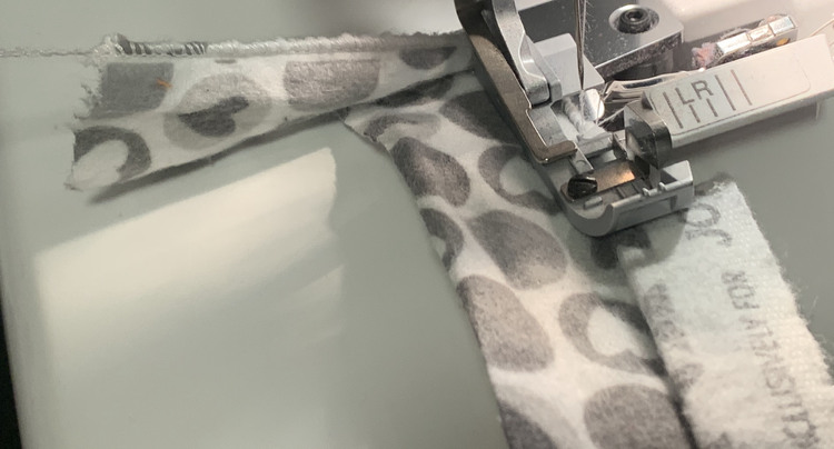 Image shows a scrap of grey hearted fabric with a rolled hem behind the serger foot and a selvedge edge in front of the foot.