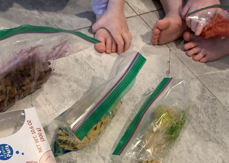 Image shows a mixed sealed bag of purple pasta on the left, two bags of unmixed dyed pasta in the center, and a red bag of pasta in the corner being mixed by a kid.