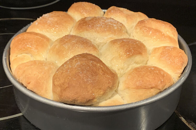 Image shows a metal cake pan filled with browned and rounded buns all baked together.
