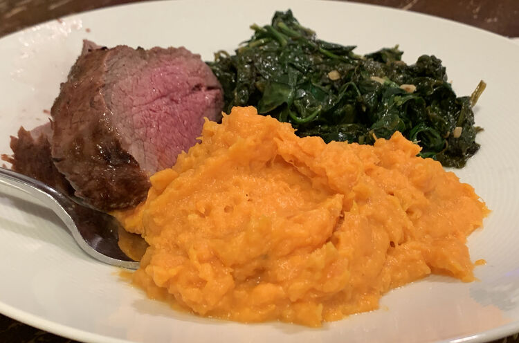 Closeup of a plate with three piles centered in the middle. On the left is perfectly made two thick slices of tri-tip, a pile of green, and, in the front, a pile of the recipe:  Coconut and Sweet Potato Mash.