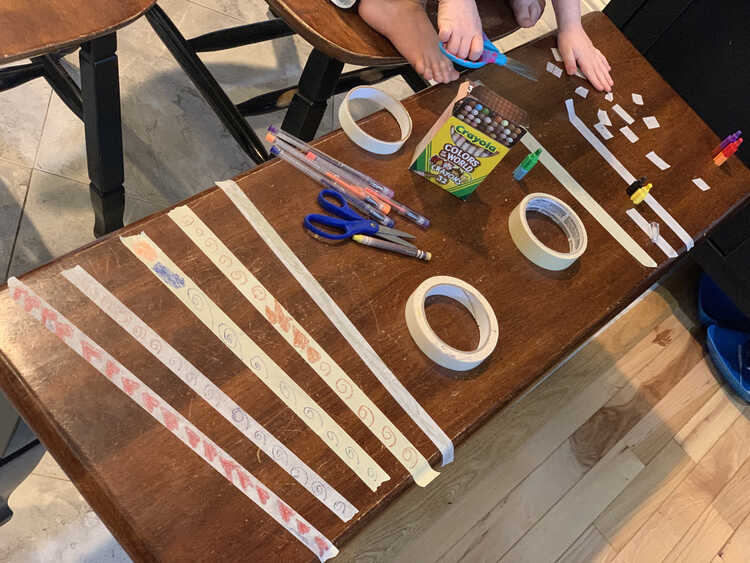 Image shows the bench festooned with many masking tape bandages. Closer to the camera are Ada's patterned strips while, in the background, you can see Zoey's hands and feet while she leans over to cut the tape smaller.